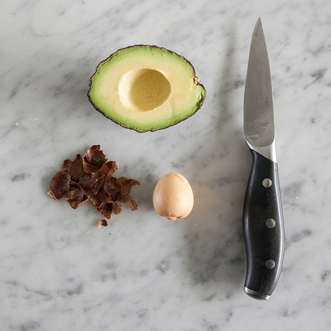 Peeling off an avocado pit with a knife, by Botanopia
