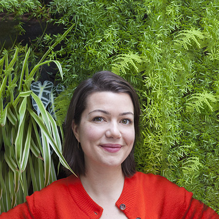 portrait of Botanopia founder in front of a plant wall